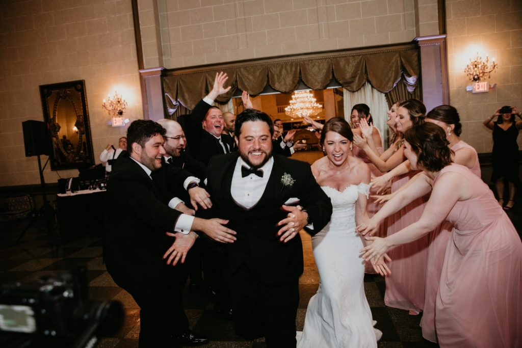 bride and groom dancing with wedding party
