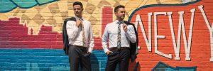 grooms posing in front of mural