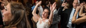 bride with hands raised while dancing