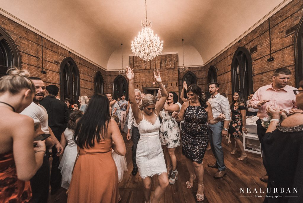 bride with hands raised dancing with friends